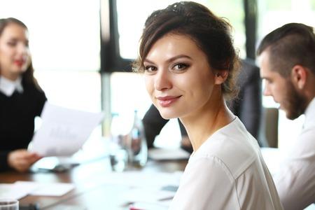GERENTE: Mujer de negocios con su personal, el grupo de personas en el fondo en la oficina moderna brillante en interiores