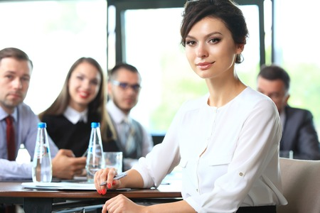 team leader: business woman with her staff, people group in background at modern bright office indoors Stock Photo