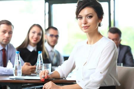 lider: Mujer de negocios con su personal, el grupo de personas en el fondo en la oficina moderna brillante en interiores