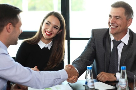 personas trabajando: La gente de negocios dándose la mano, terminando una reunión