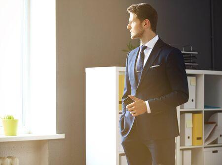 empresario: Apuesto hombre de negocios mirando por la ventana