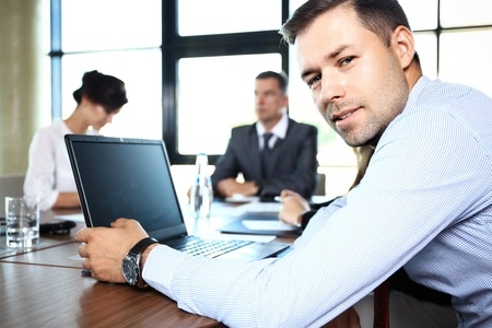 confident business woman: Businessman with colleagues in the background
