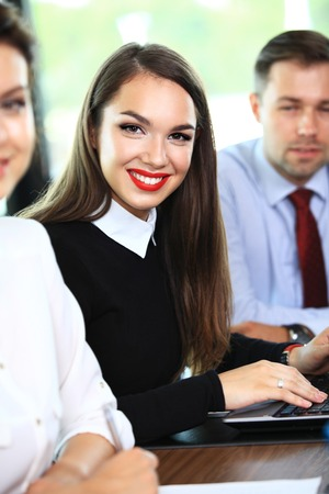 business people meeting: business woman with her staff, people group in background at modern bright office indoors Stock Photo