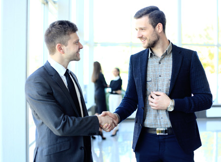 happy customer: businesss and office concept - two businessmen shaking hands in office