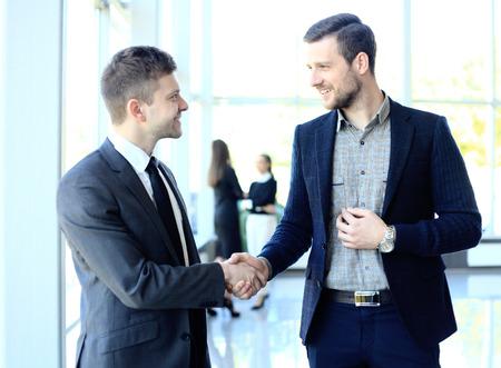 stretta mano: businesss e ufficio concetto - due uomini d'affari si stringono la mano in ufficio