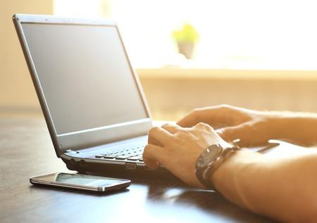 tecnolog�a informatica: El hombre manos de mecanograf�a en el teclado port�til  Foto de archivo