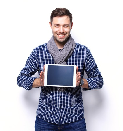 흰색 배경에 대해 태블릿 컴퓨터를 사용하여 웃는 젊은이 스톡 콘텐츠