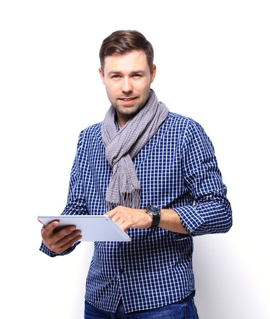 mid thirties: Smiling young man using tablet computer against a white background Stock Photo