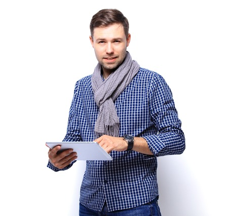 isolated man: Smiling young man using tablet computer against a white background Stock Photo