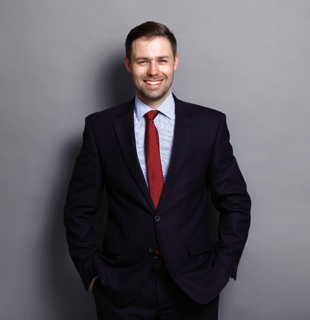 businessman suit: Cool businessman standing on grey background