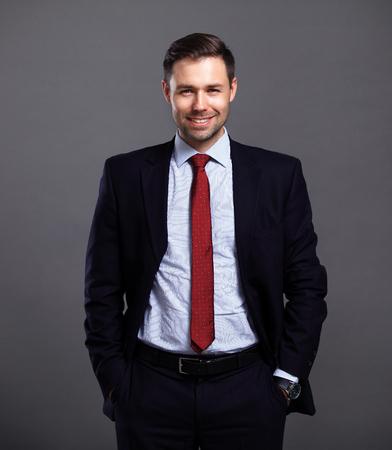 Cool zakenman die zich op een grijze achtergrond Stockfoto