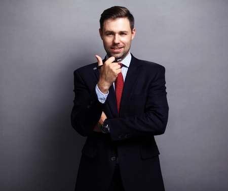 standing businessman: Cool businessman standing on grey background