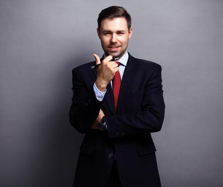 hombre de negocios: Hombre de negocios fresco de pie sobre fondo gris Foto de archivo