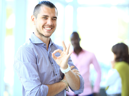 Businessman showing OK sign with his thumb up. Selective focus on face. 版權商用圖片