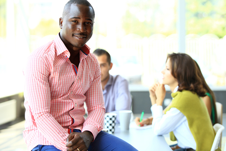 juventud: Retrato de sonriente hombre de negocios estadounidense con los ejecutivos que trabajan en segundo plano