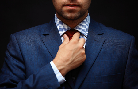 tie: Well dressed business man adjusting his neck tie