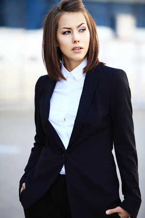 executive woman: Portrait of a successful business woman smiling. Beautiful young female executive in an urban setting