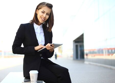 disposer: Beautiful brunette business woman working on a tablet in her hands outdoors. copy space