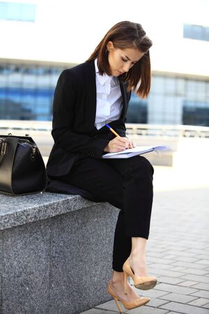 Beautiful brunette business woman working on a tablet in her hands outdoors. copy space