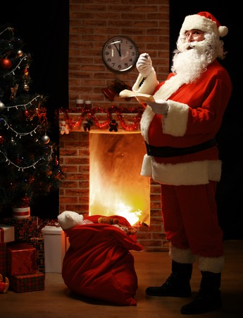 claus: Portrait of happy Santa Claus standing at his room at home near Christmas tree and big sack and reading Christmas letter or wish list