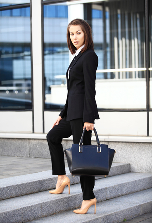 young executive: Portrait of a successful business woman smiling. Beautiful young female executive in an urban setting