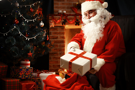 claus: Santa Claus brought gifts for Christmas and having a rest by the fireplace. Home decoration.