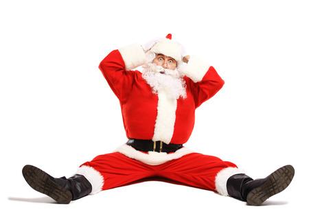 weihnachtsmann lustig: Hilaus und lustige Weihnachtsmann verwechselt, während auf einem weißen Hintergrund in voller Länge sitzt Lizenzfreie Bilder