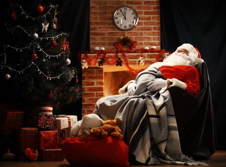 christmas tree presents: Santa Claus having a rest in a comfortable chair near the fireplace at home.
