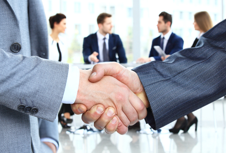 business  deal: Closeup of a business handshake. Business people shaking hands, finishing up a meeting