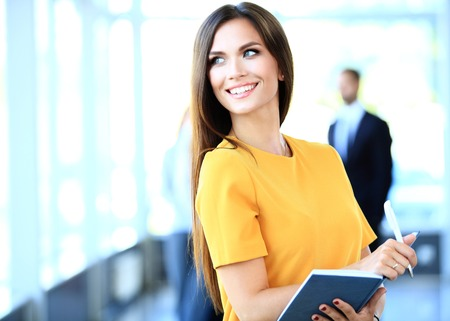 actitud: Mujer de negocios con su personal, el grupo de personas en el fondo en la oficina moderna brillante en interiores