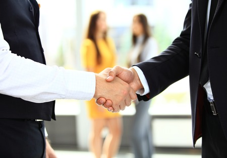 shaking hands business: businesss and office concept - two businessmen shaking hands in office