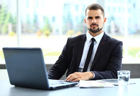 ハンサムな実業家のオフィスでノート パソコンでの作業