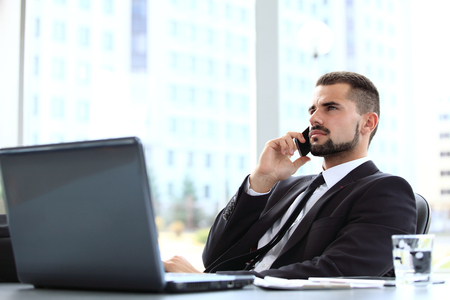 casual business: Portrait of businessman talking on mobile phone in office