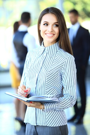 young executive: business woman with her staff, people group in background at modern bright office indoors Stock Photo
