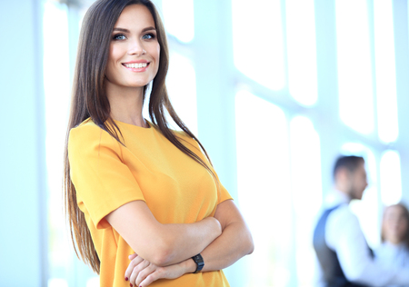 Onun personeli ile iş kadını, kapalı modern, aydınlık ofiste arka planda insanlar grubu