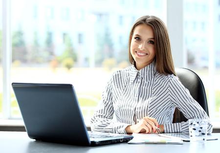 オフィスでラップトップ コンピューターに取り組んでいるビジネスの女性 写真素材