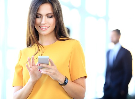 young worker: pretty businesswoman using smart phone in office