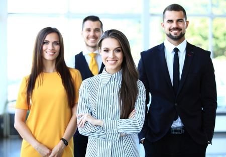 Happy business team with arms crossed at office