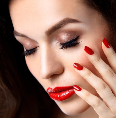 black color: Red Sexy Lips and Nails closeup. Half of Beauty model girls face isolated on black