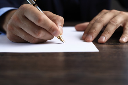 Man signing a document or writing correspondence with a close up view of his hand with the pen and sheet of notepaper on a desk top. Banque d'images