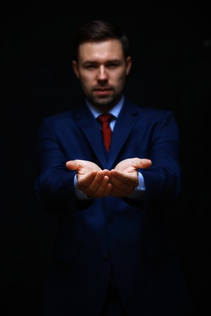 Businessman asking for money. hand symbol isolated on black