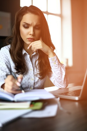 account executives: financial manager taking notes when working on report.