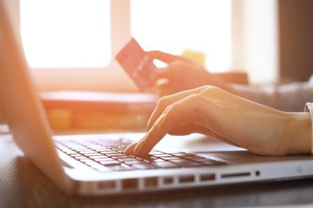 tarjeta de credito: Cerca de la mujer de compras en línea utilizando equipo portátil con tarjeta de crédito Foto de archivo