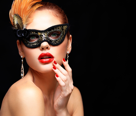 black mask: Beauty model woman wearing venetian masquerade carnival mask at party isolated on black background. Christmas and New Year celebration. Glamour lady with perfect make up Stock Photo