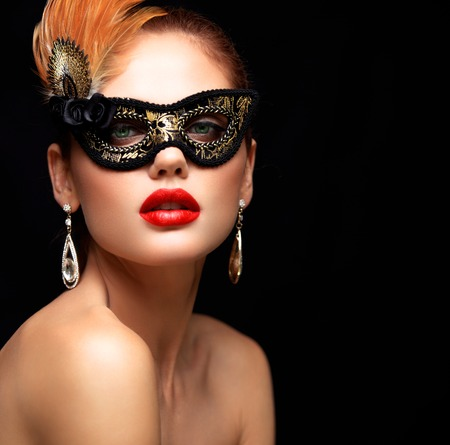 Beauty model woman wearing venetian masquerade carnival mask at party isolated on black background. Christmas and New Year celebration. Glamour lady with perfect make up Banco de Imagens