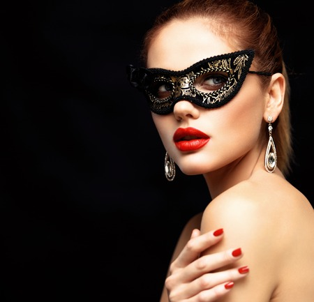 Beauty model woman wearing venetian masquerade carnival mask at party isolated on black background. Christmas and New Year celebration. Glamour lady with perfect make up 免版税图像
