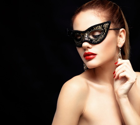 mysterious: Beauty model woman wearing venetian masquerade carnival mask at party isolated on black background. Christmas and New Year celebration. Glamour lady with perfect make up Stock Photo