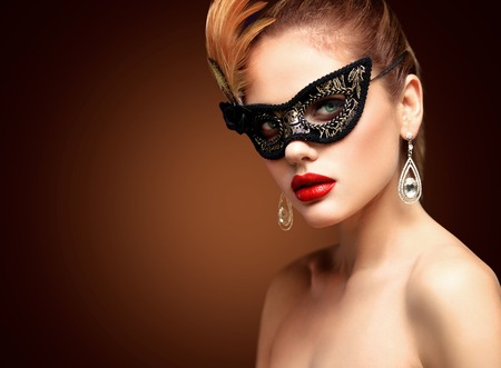 black hair: Beauty model woman wearing venetian masquerade carnival mask at party isolated on black background. Christmas and New Year celebration. Glamour lady with perfect make up Stock Photo