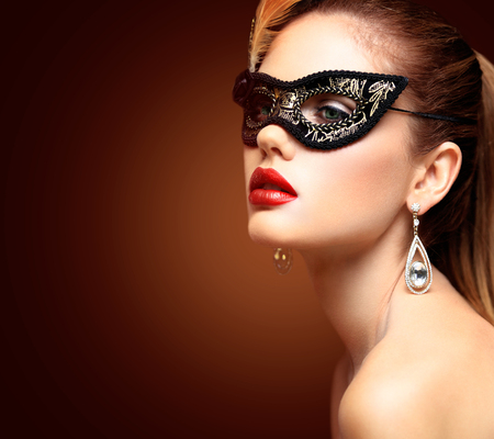 lips: Beauty model woman wearing venetian masquerade carnival mask at party isolated on black background. Christmas and New Year celebration. Glamour lady with perfect make up Stock Photo