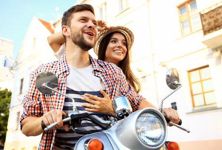 Couple in love riding a motorbike , Handsome guy and young woman travel . Young riders enjoying themselves on trip. Adventure and vacations concept.
